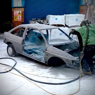Paint being removed from a car chassis using the soda blasting method